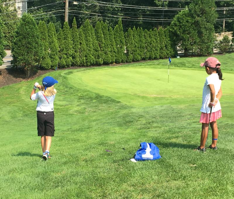 One junior golfer swinging the club while another junior golfer watches